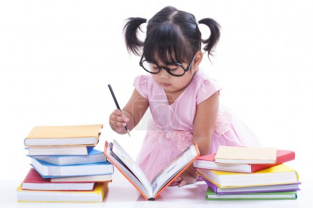Little girl writing in book