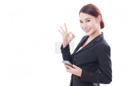Portrait of young business woman using a mobile phone and showing ok sign