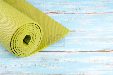 Photo for Yoga mat on a wooden background. Equipment for yoga. Concept  healthy lifestyle and sport. Lots of copy space. Selective focus - Royalty Free Image
