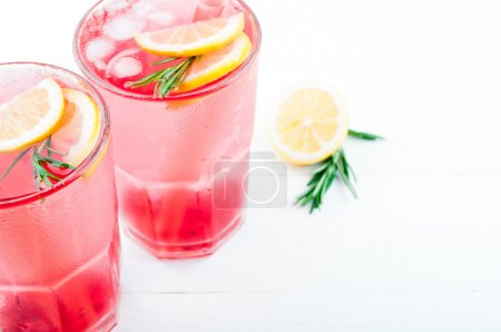 Summer drink berry lemonade cocktail with lemon and rosemary
