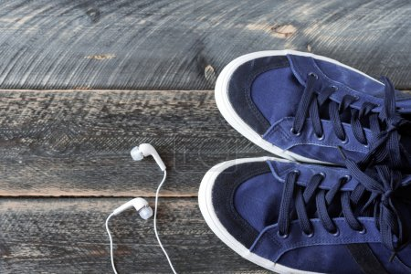 Photo for Sneakers and earphones on old wooden background top view. The image is tinted. Selective focus - Royalty Free Image