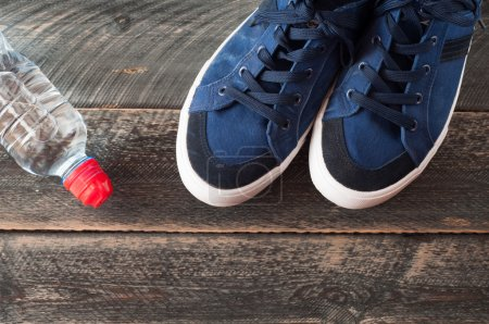 Photo for Sport shoes and water on wooden background . Sport equipment top view - Royalty Free Image