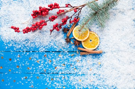 Photo pour Christmas card. Spices, orange slices, Christmas tree and berries, stars, fake snow on the wooden background. Top view - image libre de droit