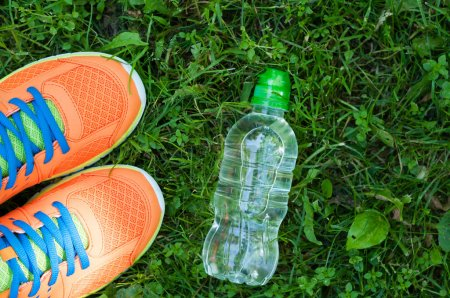 Sports shoes sneakers and bottle of water on a fresh green grass