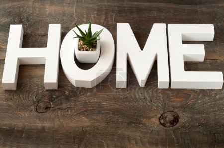 Wooden letters forming word home on wooden background.