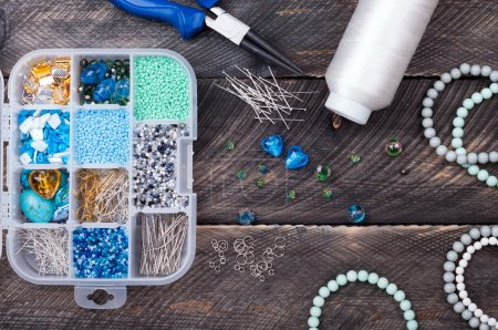 Box with beads, spool of thread, plier and glass hearts to creat