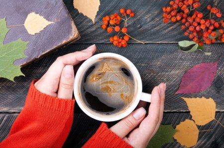 Photo pour Femme mains tenant une tasse de café sur fond de bois d'automne. Vieux livre, feuilles d'automne et rowan séché sur fond. Tasse à café confortable. Vue du dessus - image libre de droit