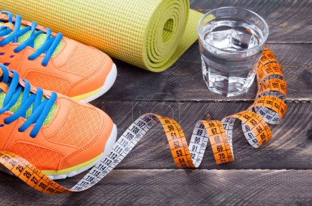 Sport shoes, yoga mat,  glass of water and centimeter on wooden
