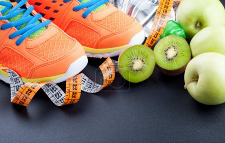 Sport shoes, fruits,  bottle of water and measuring tape on dark