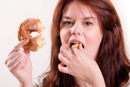Plump woman eating donut