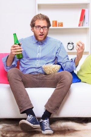 Photo pour Homme surpris devant la télé avec le pop-corn et de la bière - image libre de droit
