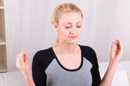 Photo for Yong woman practicing yoga at home interior - Royalty Free Image