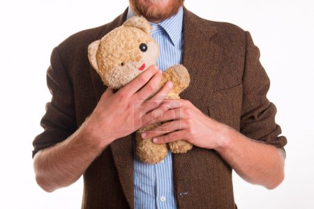 Old teddy bear in the arms of a man