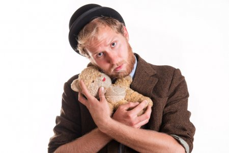 Unhappy old-fashioned man hugs an old teddy bea