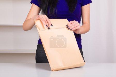 Photo pour Femme ouvrant une grande enveloppe avec des documents à la maison. mains fermées - image libre de droit