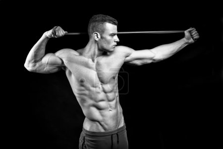 Muscular fitness man presents his body building on black backgro