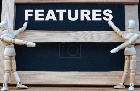 Photo pour CARACTÉRISTIQUES mot écrit sur un tableau noir. A proximité se trouvent deux hommes en bois. Concept d'entreprise. - image libre de droit
