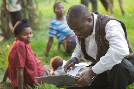 Photo pour Rdc, République démocratique du Congo. Mission de l'Unicef contre le tétanos en septembre 2008. Processus de vaccination. Un médecin de la mission de l'Unicef répond à la question du tétanos et garde des statistiques sur les personnes vaccinées. - image libre de droit