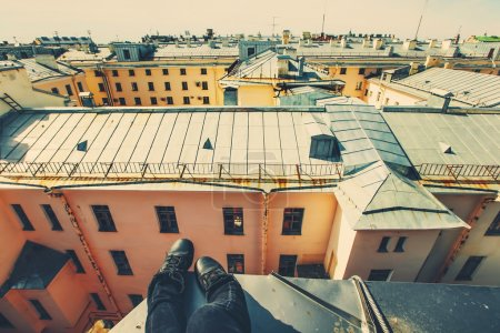 Legs of person sitting on the roof