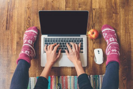 Photo pour Workspace in home: fingers on laptop keyboard, red apple, legs in socks on a wooden floor and colored carpet - image libre de droit
