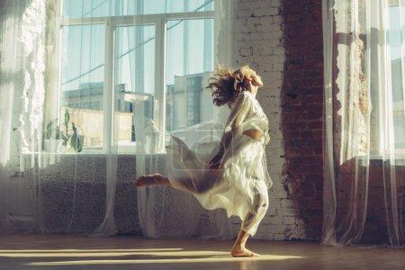 Photo pour Belle femme à l'intérieur lumineux avec de grandes fenêtres écoutant de la musique et dansant. Concept confort à domicile - image libre de droit