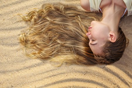 Woman hair in sand