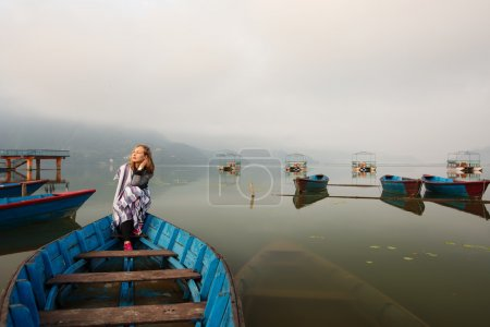 girl sitting in old boat on mountain lake early morning