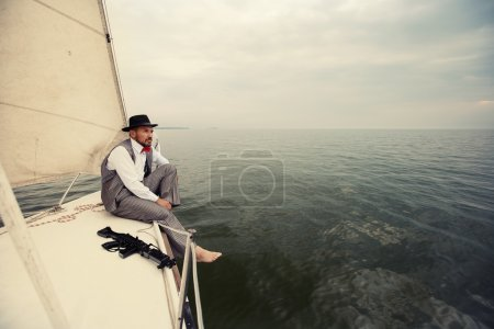 Gangster mafia man siting outdoor on yacht boat