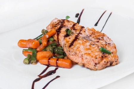 Photo pour Saumon grillé avec asperges, carottes et sauce. Plat isolé sur fond blanc - image libre de droit
