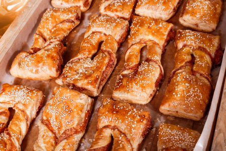Delicious Puff pastry with cheese filling and sesame seeds on shelf in Bakery shop. Pastries and bread in a bakery