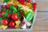 čerstvé bio cherry rajčátky a pasta s česnekovou bazalkovým na tmavém pozadí
