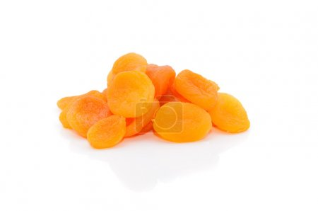 A heap of dried apricots on a white background with a light shad
