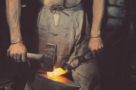 Blacksmith working metal with hammer on the anvil ...