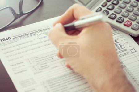 Photo pour Homme remplissant le formulaire de déclaration de revenus des particuliers - image libre de droit
