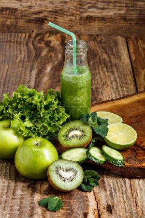 Photo pour Les bouteilles avec frais jus de fruits légumes et kiwi sur table en bois. Régime détox. - image libre de droit