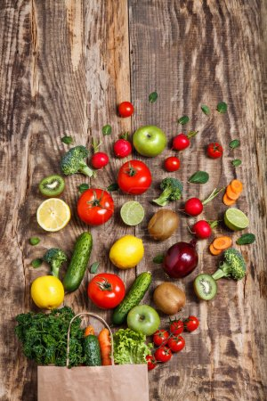 Photo for The fresh vegetables and fruit from a paper bag on a wooden table - Royalty Free Image