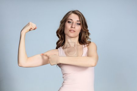 Photo for The young woman showing her muscles on gray background. Strength and power concept - Royalty Free Image