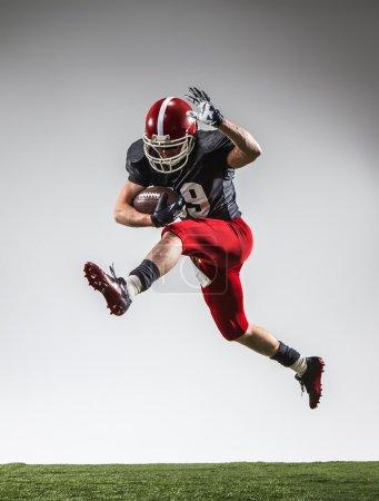 Photo pour Le joueur de football américain en action sur l'herbe verte et fond gris. - image libre de droit