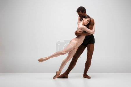 Photo for Couple of ballet dancers dancing over gray background - Royalty Free Image
