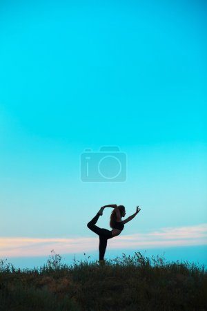 Silhouette of young woman is practicing yoga at su...