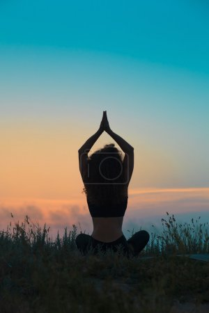 Photo pour Silhouette de jeune femme pratique le yoga au coucher du soleil - image libre de droit