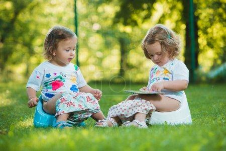 Photo pour Les deux petites filles de deux ans assis sur des pottys sur l'herbe verte de la pelouse - image libre de droit