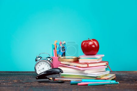 Photo for Back to School concept. Books, colored pencils and clock on blue background - Royalty Free Image