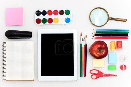 Photo pour Ensemble scolaire avec inscription de retour à l'école, cahiers, tablette, crayons, pinceau, ciseaux et pomme sur fond blanc - image libre de droit