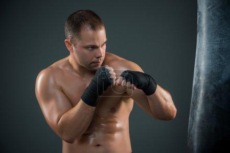 Photo pour Jeune boxeur en rouges gants de boxe sur fond noir - image libre de droit