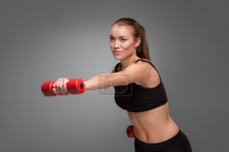 Photo for Sporty woman doing aerobic exercise with red dumbbells on grey background - Royalty Free Image