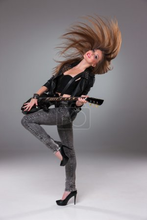 Photo for Beautiful girl  with long hair playing guitar in rock style on a gray background - Royalty Free Image