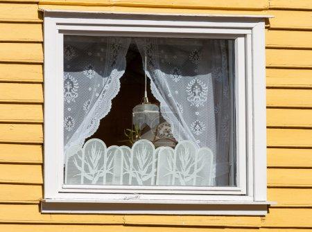 ventana en una casa de madera con cortinas blancas
