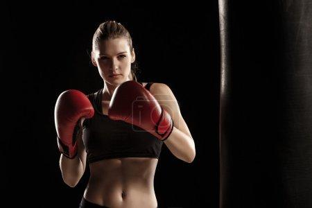 Photo pour Belle femme avec les gants rouges est boxe sur fond noir - image libre de droit