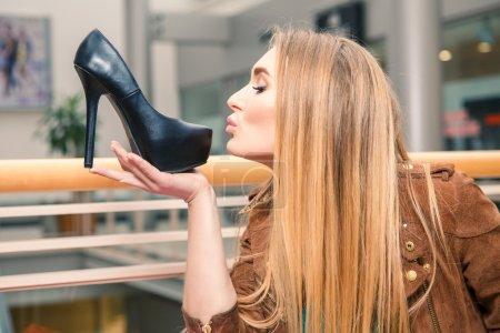 Woman kissing shoe. Women loves shoes concept.
